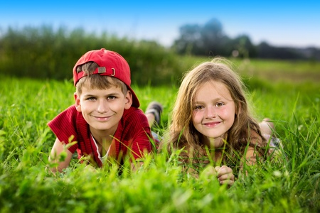 Image of two happy children having fun in the park, brother and sister lying down on green grass, best friends playing outdoors in spring, adorable little girl with cute boy enjoying springtime nature Stock Photo - 21000386