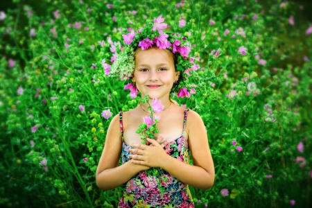 Little girl with a wreath on a head and bouquet in hands photo
