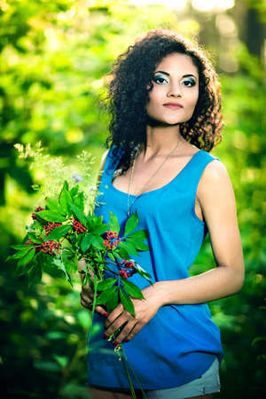 Young happy woman holding big bouquet of spring flowers outdoors. photo