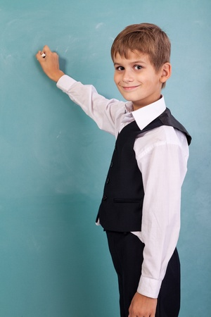 Very cute and positive student is smiling and writing on school blackboard photo