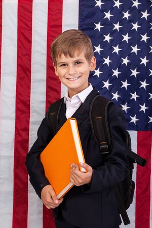 Сute schoolboy is holding an orange book against USA flag photo