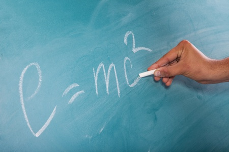 mathematical proof: Male hand is writing Einsteins Formula E=mc2 on a blackboard