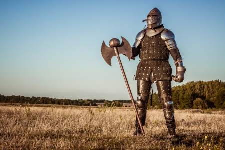 Medieval knight in the field with an axe 스톡 콘텐츠