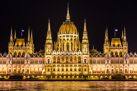 Budapest Parliament in Hungary at night, reflections on the Danube river waters. photo