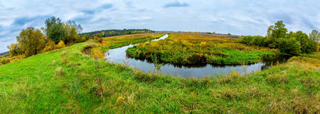 Autumn landscape, colorful leaves on trees, morning at river after rainy night. Panorama photo