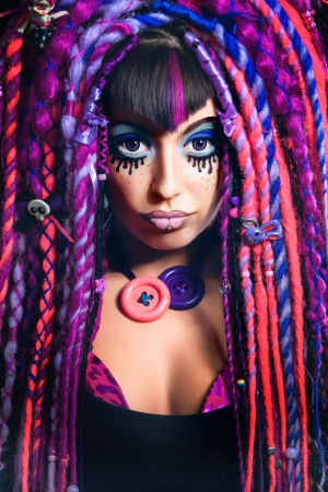 Portrait of a stylish young woman with multicolored dreadlocks and with stylish make-up in doll style. Creative make-up.Fantasy dress. photo