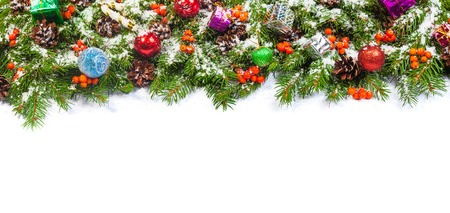 Christmas background with balls and decorations and snow, holly berry, cones isolated on white