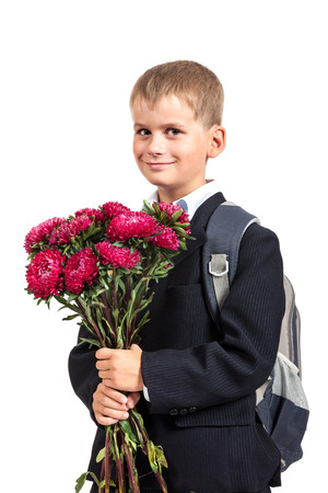 Handsome little schoolboy is holding flowers isolated on white background. Back to school photo