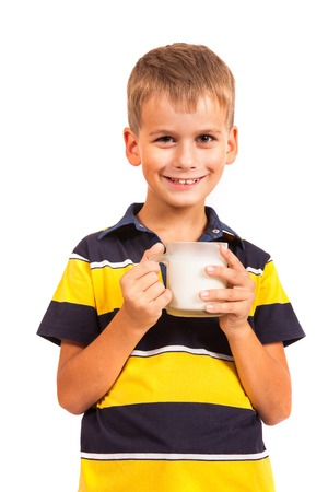 �ute boy is drinking milk. Schoolboy is holding a cup of milk isolated on a white background photo