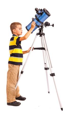 Niño que mira a Star Gazing Telescopio Little Boy aislado en un fondo blanco Foto de archivo