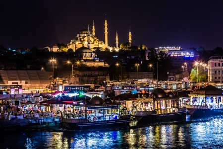 suleyman: ISTANBUL - APRIL 30: Night view on the restaurants at the end of the Galata bridge, Sultanahmet, at sunset with the famous Suleymaniye Mosque in the background, Istanbul, Turkey, APRIL 30, 2013