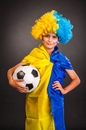Football fan with a blue and yellow ukrainian flag painted on his face on black background photo
