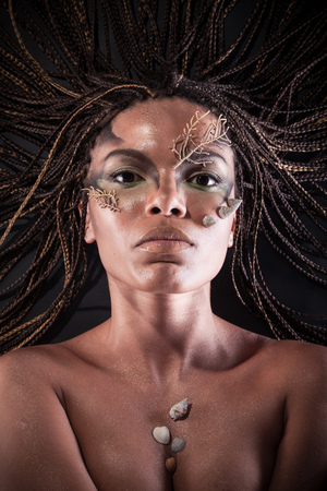 Portrait of a beautiful naked young african american woman with dreadlocks hair lying   on a black background photo