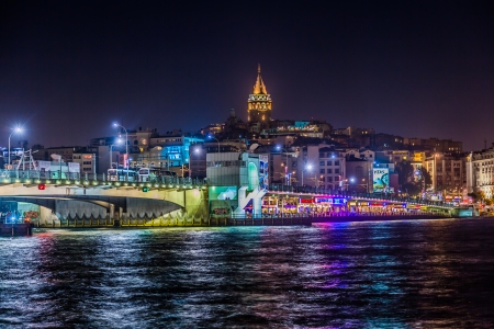 ISTANBUL, TURKEY - MAY 27: Night view of Galata bridge and Tower on May 27, 2013 in Istanbul, Turkey. Galata bridge spans the Golden Horn and has fish restaurants and shops on first floor.