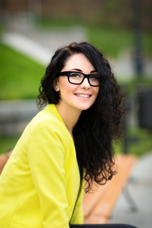 portrait of young woman smiling with glasses against a plants background photo