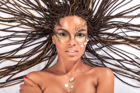 Portrait of a beautiful naked young african american woman with dreadlocks hair lying   on a white background photo