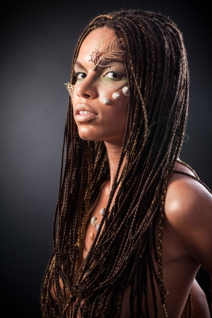 Portrait of a beautiful naked young african american woman with dreadlocks hair  on a black background photo