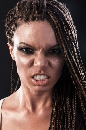 Portrait of an angry african american woman with dreadlocks hair  on a black background photo