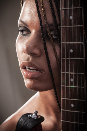 Portrait of a beautiful young african american woman with dreadlocks hair with an electric guitar on a black background photo
