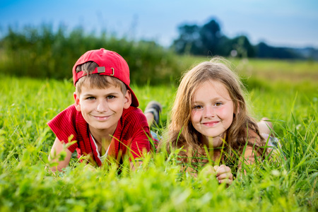 Image of two happy children having fun in the park, brother and sister lying down on green grass, best friends playing outdoors in spring, adorable little girl with cute boy enjoying springtime nature photo