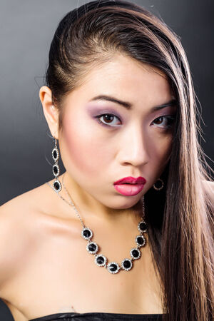 Beauty Portrait. Beautiful brunette Asian woman with long black hair. Shot in a studio on a black background photo