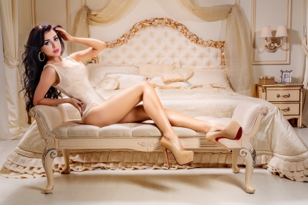 Beautiful and attractive young adult female brunette sensuality woman posing on bed in exclusive apartment Stock Photo