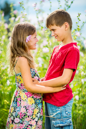 Portrait of a cheerful girl and boy hugging fun in outdoor photo