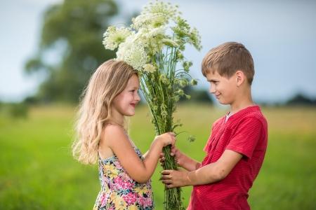 romance: paar in de liefde, jongen geeft een meisje een boeket van wilde bloemen