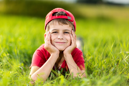 happy little boy laying on the grass photo
