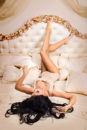 Photo of sexy brunette woman lying in big bed photo