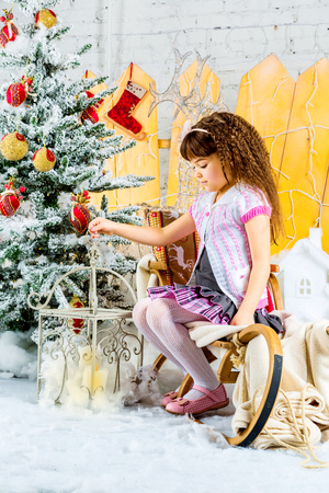 Little girl on sledge under the Christmas tree photo