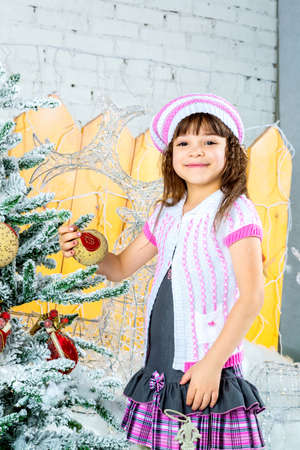 Cute little girl is  decorating the christmas tree photo