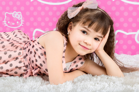 Little cute girl is on the fur carpet on pink background photo