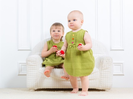Two little kids sit on a sofa and play photo