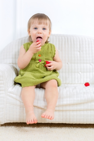 little kid sit on a sofa and eating strawberries photo