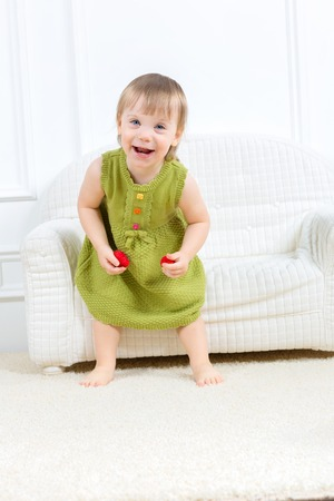 little kid sit on a sofa and play photo