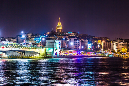 first floor: ISTANBUL, TURKEY - MAY 27: Night view of Galata bridge and Tower on May 27, 2013 in Istanbul, Turkey. Galata bridge spans the Golden Horn and has fish restaurants and shops on first floor.