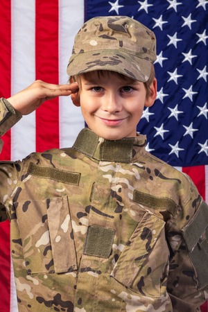 Young boy dressed like a soldier with American flag in background. photo