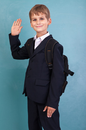 �ute schoolboy show sign hello against school blackboard photo