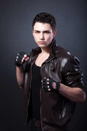 agressive: Agressive muscular young man on a black background.