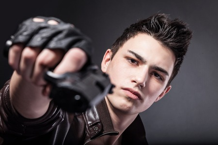 Aiming. Serious man with a gun on a black background Stock Photo
