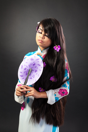Beautiful asian woman wears a national dress is holding a fan, isolated on a black backround photo