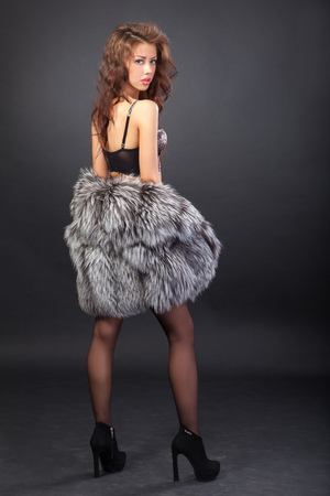Attractive woman in fur coat and bra. Shot in a studio on a black background photo