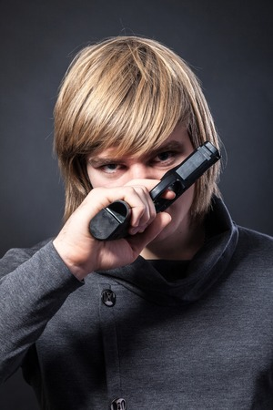 Aiming. Serious man with a gun on a black background photo