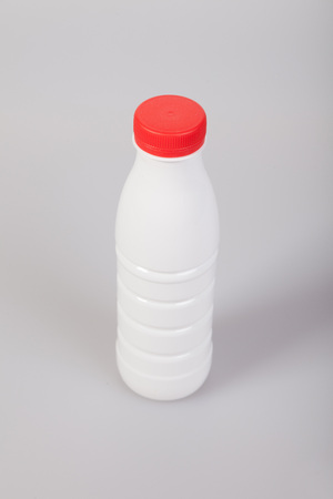 White Yogurt Plastic Bottle with red cap on a white background photo
