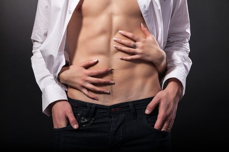 Womans hands on a sexy mans torso on a black background