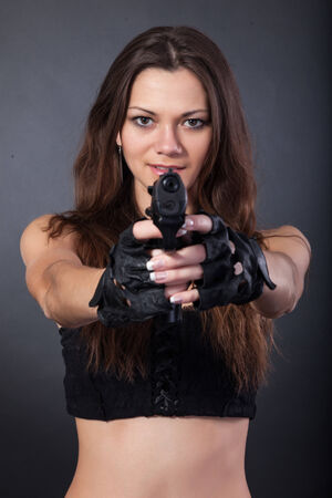 Beautiful sexy police girl with handgun and  isolated on grey background photo