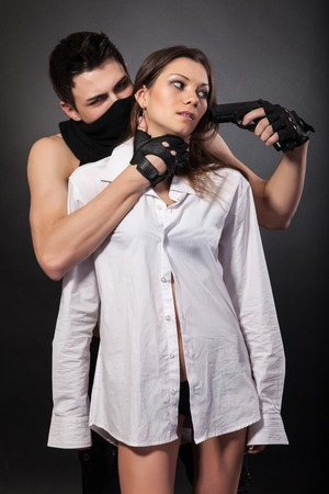 Man take a beautiful woman as a hostage isolated on a white background Stock Photo