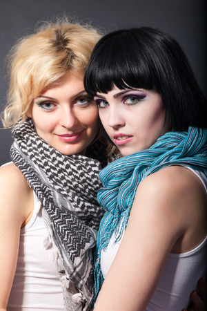 Two young attractive lesbians are hugging isolated on gray background photo
