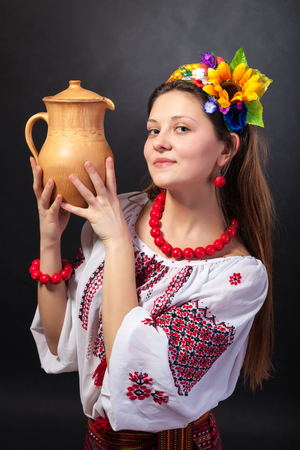 Attractive woman wears Ukrainian national dress is holding a jug isolated on a black background photo